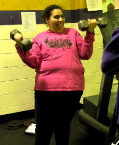 Photo of Mona Rabie with a big smile on her face as she works out with free weights.